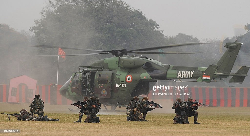 Soldiers take position while performing a drill after alighting from an HAL Dhruv helicopter during an Army weaponry exhibition in Kolkata on February 2, 2013. The event was held as a recruitment tool for young Indians to join the country's armed forces. AFP PHOTO/Dibyangshu SARKAR