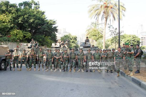 Soldiers take security measures as protesters stage a protest after the Lebanese judiciary on Friday handed down death sentences against two...