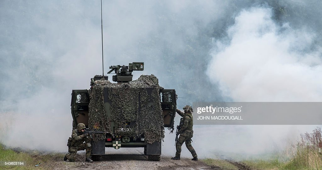 Soldiers take up position next to a light armoured vehicle after an ambush was simulated during a drill at the headquarters of the 33rd Panzergrenadier bataillon in Neustadt am Ruebenberge on June 29, 2016. / AFP / JOHN
