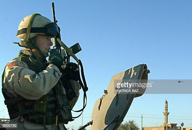 US soldiers talks on his radio as a Kiowa reconnaissance helicopter flies over Baghdad's alShowla neighborhood 05 April 2004 Pitched battles in...