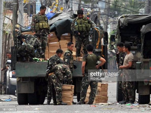 Soldiers unload ammunitions near the site of a standoff as firefighting between government troops and remnants of Muslim rebels rages on with the...