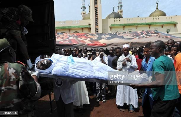 Soldiers unload bodies of victims shot dead by Guinea junta forces at the September 28 2009 demonstration in front of the Conakry great mosque on...