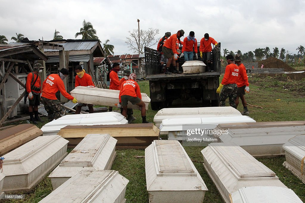 Soldiers unload coffins containing dead bodies from their truck on December 14, 2012 in the heavily devastated town of New Bataan, Compostela Valley province, Philippines. More than 900 people have been killed and nearly a thousand others remain missing after Typhoon Bopha, the strongest storm to hit the Philippines this year, pounded the region.