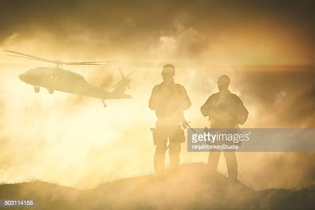 Soldados esperar de un helicóptero en vendaval de polvo