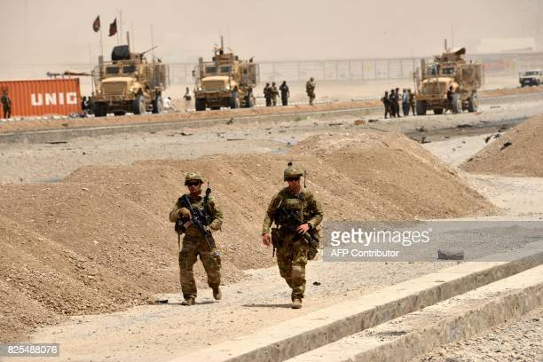 US soldiers walk at the site of a Taliban suicide attack in Kandahar on August 2 2017 A Taliban suicide bomber on August 2 rammed a vehicle filled...