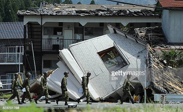 TOPSHOT Soldiers walk before a collapsed house to search for missing people in MinamiAso Kumamoto preficture on April 22 2016 While the death toll...