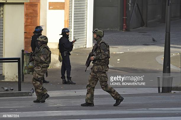 Soldiers walk by policemen as they patrol in the northern Paris suburb of SaintDenis city center on November 18 as French Police special forces raid...