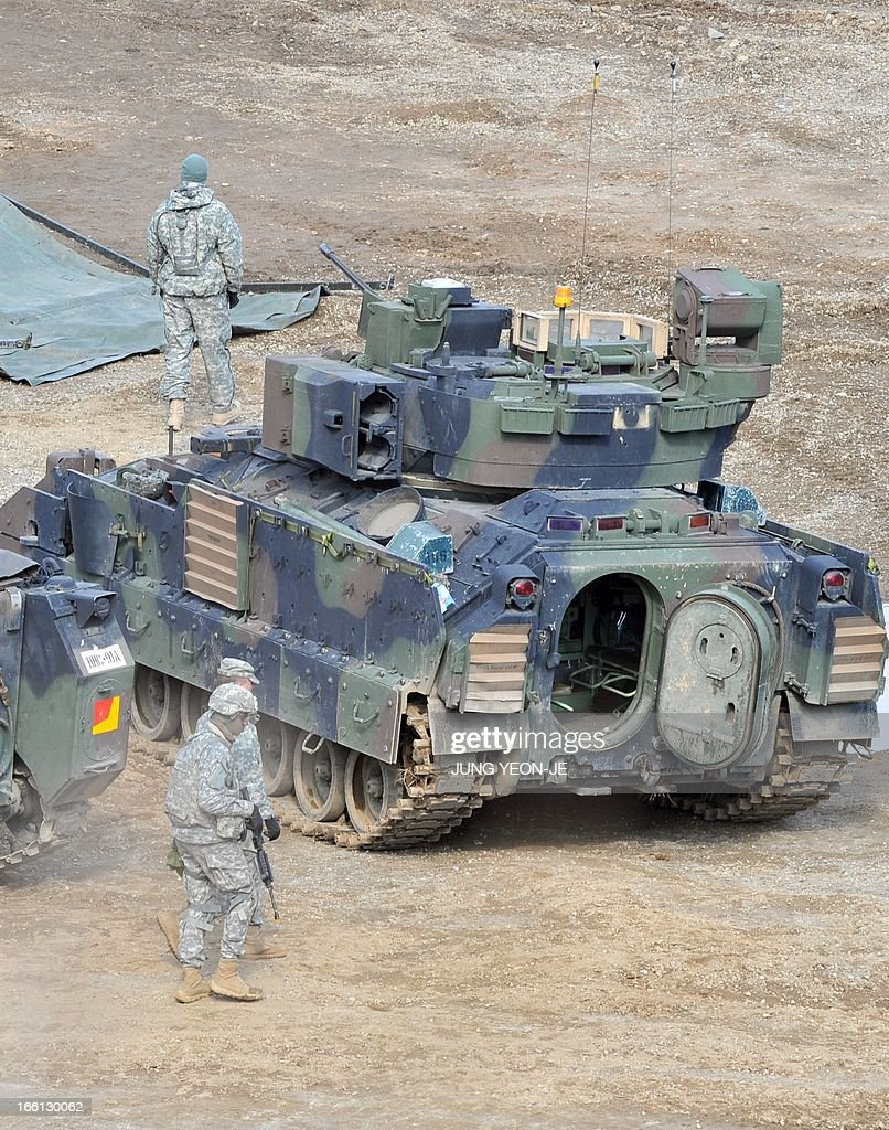 US soldiers walk past a Bradley armored vehicle at a military training field in the border city of Yeoncheon, northeast of Seoul, on April 9, 2013. North Korea said on April 9 the Korean peninsula was headed for 'thermo-nuclear' war and advised foreigners in South Korea to consider evacuation -- a warning that was largely greeted with indifference. AFP PHOTO / JUNG YEON-JE