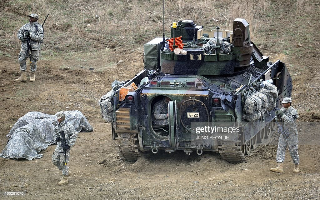 US soldiers walk past a Bradley armored vehicle at a military training field in the border city of Yeoncheon, northeast of Seoul, on April 11, 2013. The United States has warned North Korea it is skating a 'dangerous line' with an expected missile launch that could start a whole new cycle of escalating tensions in a region already on a hair-trigger.