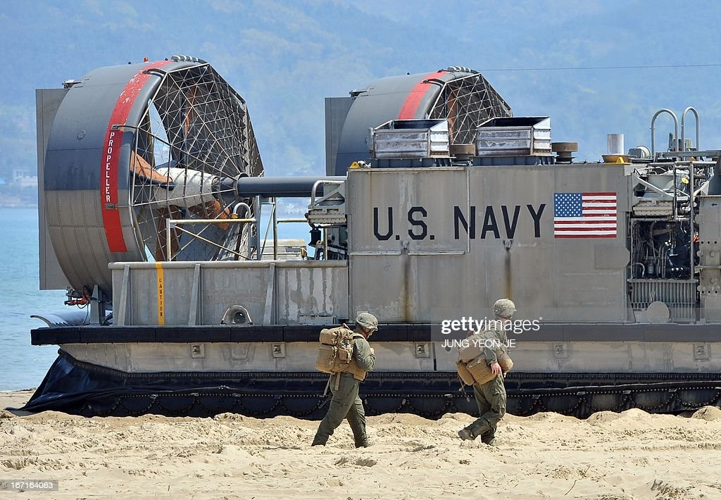 US soldiers walk past a US Navy landing craft air cushion (LCAC) at a beach during the Combined Joint Logistics Over the Shore (CJLOTS) exercise in Pohang, 260 kms southeast of Seoul, on April 22, 2013. The wait for North Korea's expected missile test, which has kept South Korean and US forces on heightened alert for the past two weeks, may stretch to July, the South's defence ministry said on April 22.