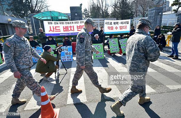 US soldiers walk past South Korean antiwar activists holding a rally against talks on deploying the Terminal High Altitude Area Defence System...