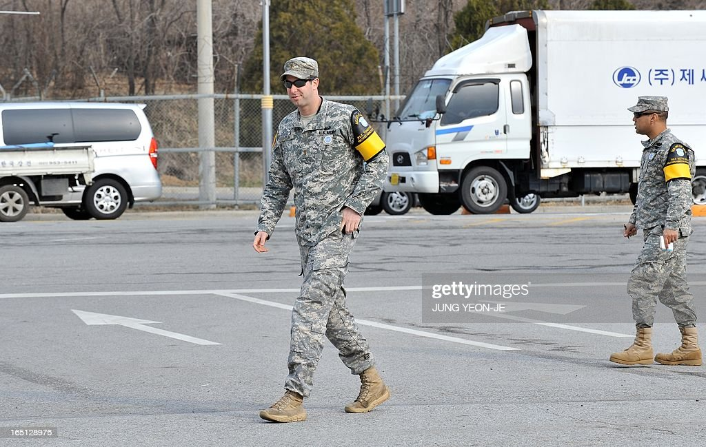 US soldiers walk past South Korean vehicles leaving for North Korea at the inter-Korean transit office in Paju near the Demilitarized Zone (DMZ) on April 1, 2013. South Korean workers and cargo on April 1 headed for the Kaesong Industrial Complex without a hitch despite North Korea's recent threat to close the joint industrial zone in the communist country.