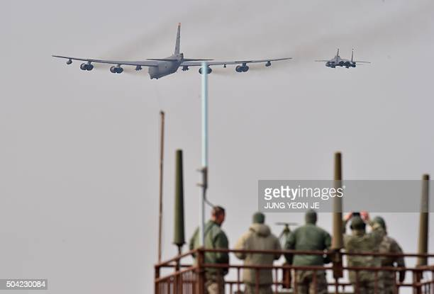 US soldiers watch a US B52 Stratofortress being escorted by a South Korean F15K fighter jet as it flies over the Osan Air Base in Pyeongtaek south of...