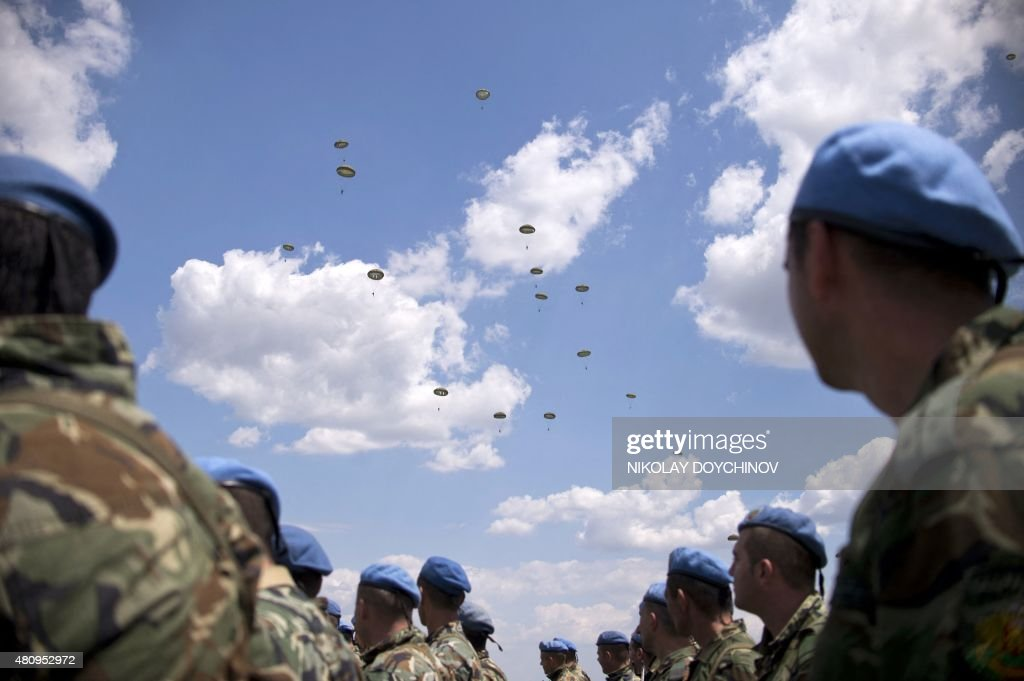 Soldiers watch paratroopers participating in a joint Bulgarian and US Air Forces military exercise called 'Thracian Summer 2015' in Plovdiv some 150...