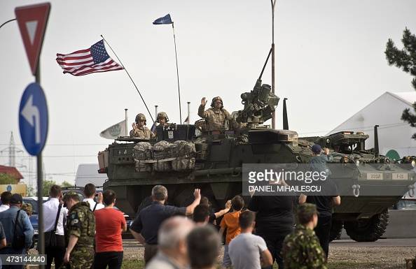 US soldiers wave from an armored vehicle in Ploiesti on May 13 2015 Some 400 US soldiers from the 2nd Cavalry Regiment 2nd Battalion of the US Army...