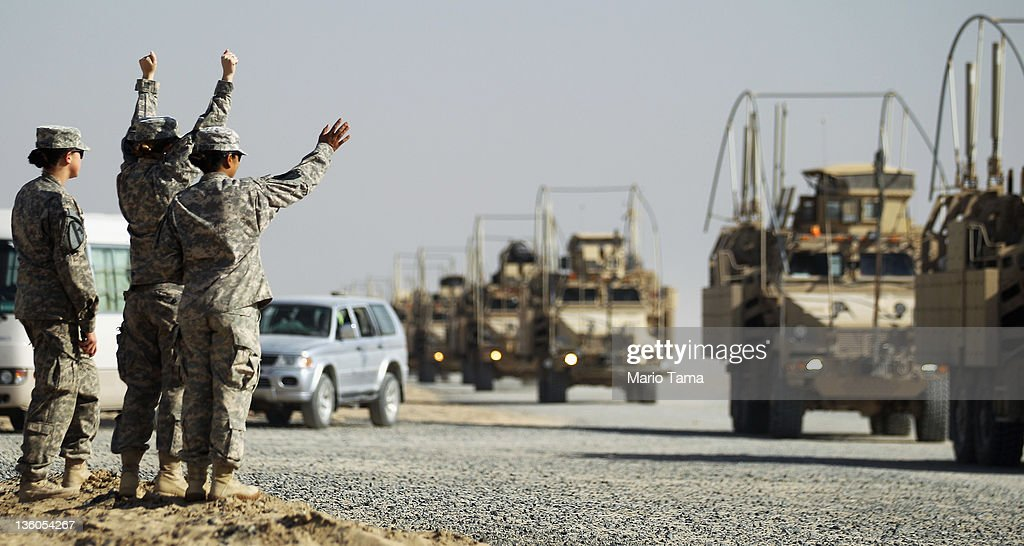 Soldiers wave to colleagues as a section of the last American military convoy to depart Iraq from the 3rd Brigade 1st Cavalry Division arrives after...