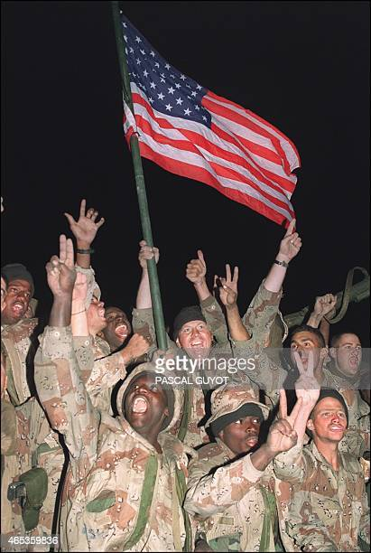 US soldiers wave US flag and flash the peace sign as they cheer the allied forces arriving in the outskirts of Kuwait City 27 February 1991