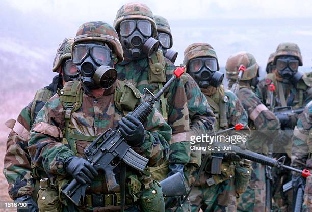 S soldiers wear gas masks as they take part in a chemical biological and radiological warfare exercise February 26 2003 in Yonchon near the...
