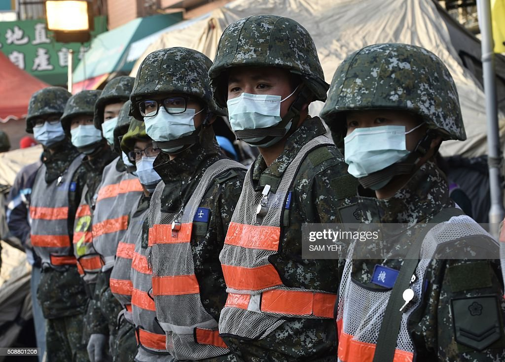 Soldiers wearing facemasks line up near the Wei-kuan apartment complex to help with the second day of rescue operations following a 6.4 magnitude earthquake in southern Taiwan's city of Tainan on February 7, 2016. Rescuers searched through the night hoping to free residents trapped in buildings toppled by the deadly earthquake in Taiwan, as survivors recalled being plucked to safety from their ruined homes. AFP PHOTO / Sam Yeh / AFP / SAM YEH