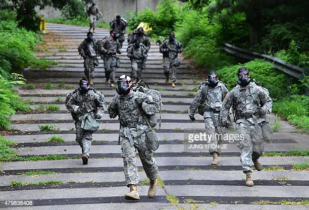 US soldiers wearing gas masks march during a competition to test individual skills at a US Army base in Uijeongbu north of Seoul on July 8 2015 The...