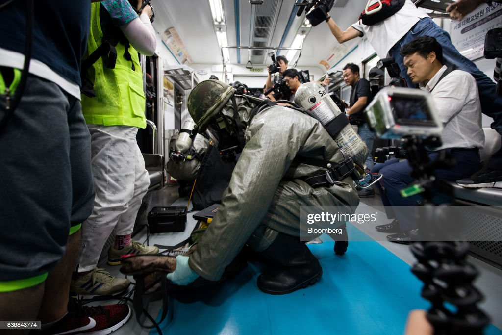 Soldiers wearing gas masks perform inspections inside a subway train during an anti-terror drill on the sidelines of the Ulchi Freedom Guardian (UFG) military exercises at a subway station in Seoul, South Korea, on Tuesday, Aug. 22, 2017. North Korea warned the U.S. on Tuesday it will face 'merciless revenge' for ignoring Pyongyangs warnings over annual military drills with South Korea. Photographer: SeongJoon Cho/Bloomberg via Getty Images