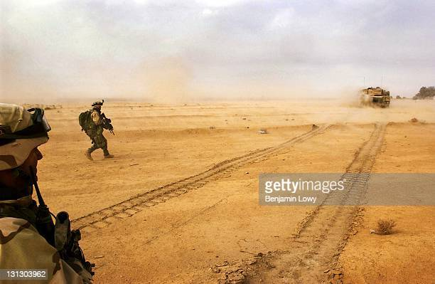 Soldiers with the 1st Brigade of the 101st Airborne Division run behind tanks during an assualt on a complex used by Iraqi soldiers launching mortars...