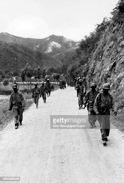 US soldiers with the 24th Infantry Regiment walk to the front lines in the Korean War Korea August 12 1950