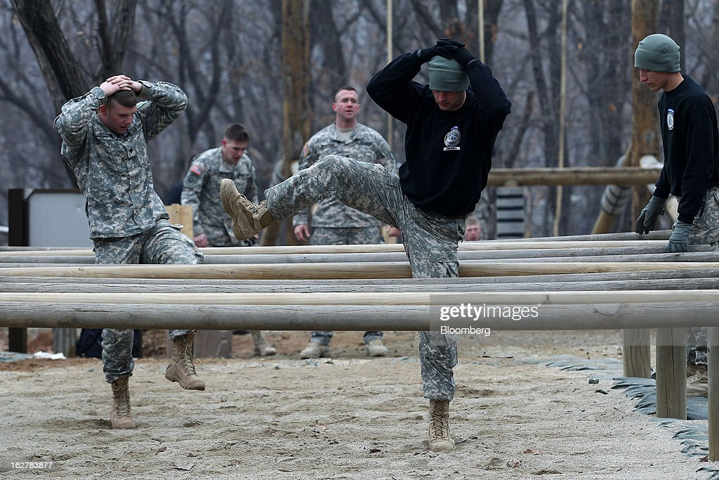 Soldiers with the U.S. Army's Second Infantry Division climb over obstacles during an air assault training course at Camp Casey in Dongducheon, South Korea, on Tuesday, Feb. 26, 2013. The U.S. has 28,500 soldiers in South Korea as a legacy of the 1950-53 Korean War, which ended in a cease-fire that left the two Koreas technically still at war. Photographer: SeongJoon Cho/Bloomberg via Getty Images