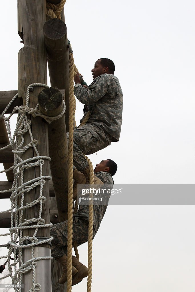 Soldiers with the U.S. Army's Second Infantry Division climb up an obstacle during an air assault training course at Camp Casey in Dongducheon, South Korea, on Tuesday, Feb. 26, 2013. The U.S. has 28,500 soldiers in South Korea as a legacy of the 1950-53 Korean War, which ended in a cease-fire that left the two Koreas technically still at war. Photographer: SeongJoon Cho/Bloomberg via Getty Images