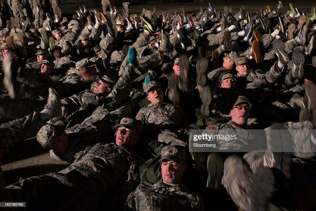 Soldiers with the U.S. Army's Second Infantry Division perform warm-up exercises during an air assault training course before dawn at Camp Casey in Dongducheon, South Korea, on Tuesday, Feb. 26, 2013. The U.S. has 28,500 soldiers in South Korea as a legacy of the 1950-53 Korean War, which ended in a cease-fire that left the two Koreas technically still at war. Photographer: SeongJoon Cho/Bloomberg via Getty Images