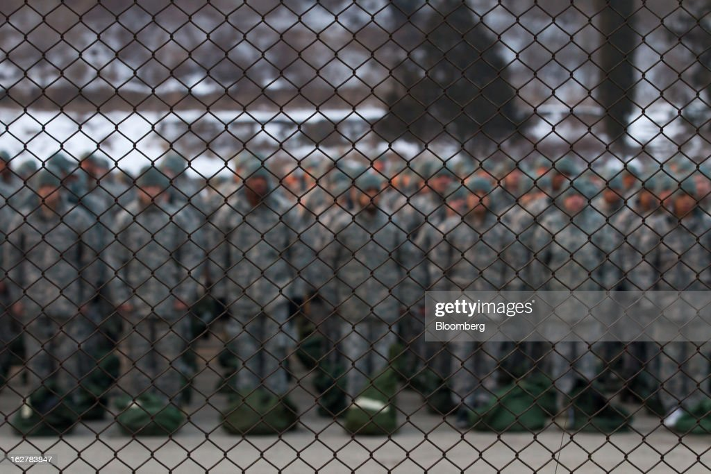 Soldiers with the U.S. Army's Second Infantry Division stand behind wire fencing during an air assault training course at Camp Casey in Dongducheon, South Korea, on Tuesday, Feb. 26, 2013. The U.S. has 28,500 soldiers in South Korea as a legacy of the 1950-53 Korean War, which ended in a cease-fire that left the two Koreas technically still at war. Photographer: SeongJoon Cho/Bloomberg via Getty Images