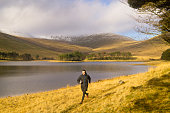 A Solo male trail running alongside lake in the Brecon Beacons National Park with Pan-Y-Fan in the background.