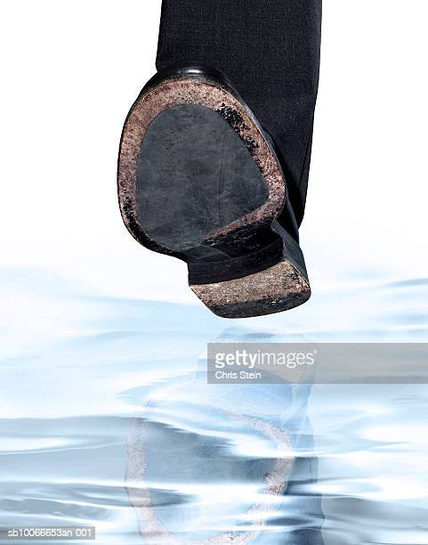 Sole of shoe stepping over water, studio shot
