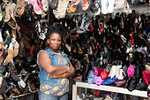 Sole trader stands in front of her shoe shop