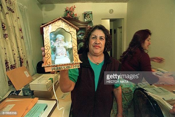 WITH 'UNA HUMILDE CASA DE EL BARRIO CONVERTIDA EN CASILLA ELECTORAL' BY C RAHOLA Soledad Ramblaz displays athe effigy of 'El Nino de Atocha' a sacred...