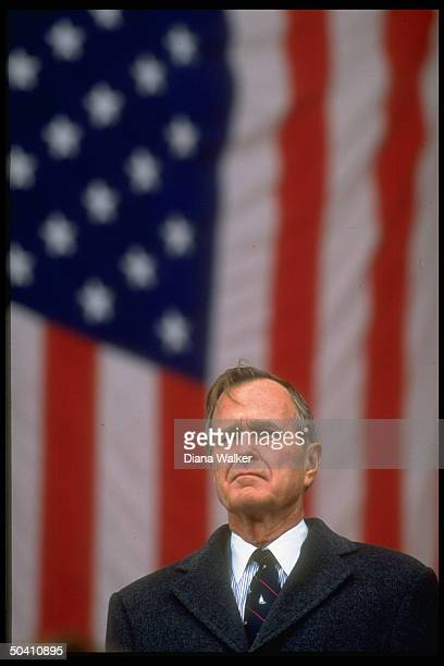 Solemn Pres George Bush in serious portrait backdropped by American flag during Veterans Day observances