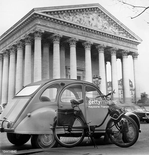 A solex bike and a citroen 2cv car are parked in front of the Madeleine Church in Paris