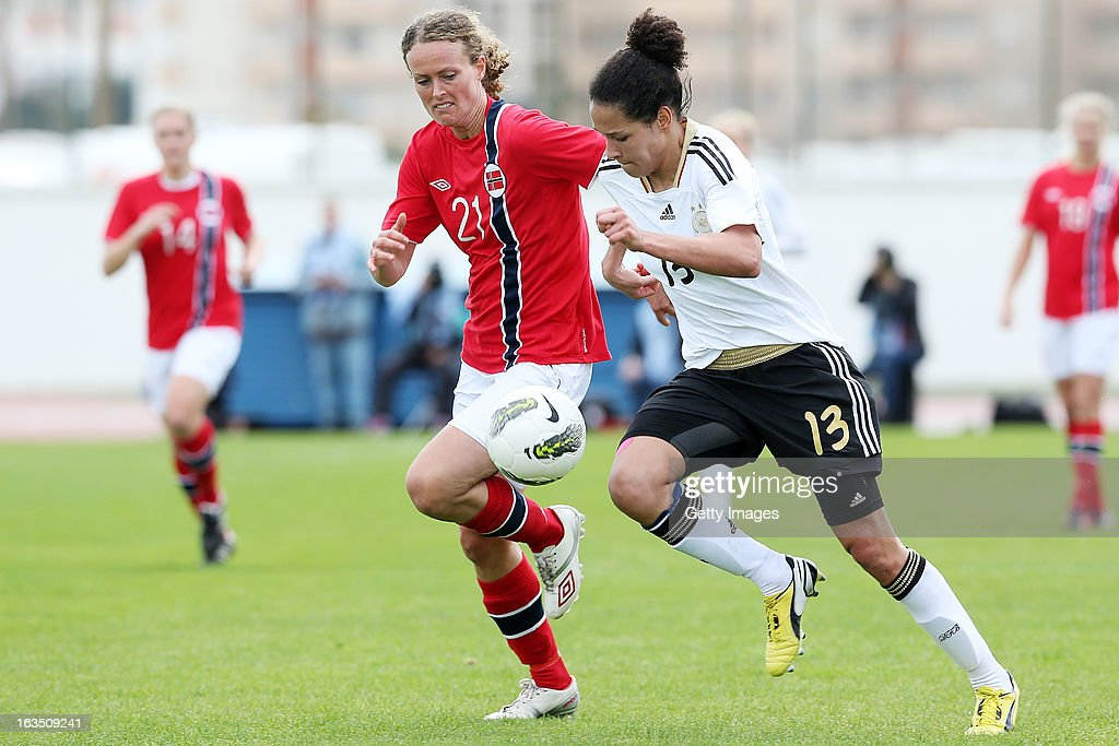 Solfrid A. Dahle #21 of Norway challenges Celia Okoyino Da Mbabi #13 of Germany during the Algarve Cup 2013 match between Norway and Germany at the Estadio Municipal de Lagos on March 11, 2013 in Lagos, Portugal.