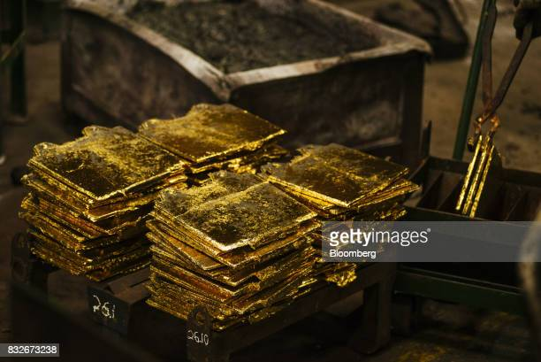 Solid gold slabs sit in piles following the electro refining process to remove impurities at the Rand Refinery Ltd plant in Germiston South Africa on...