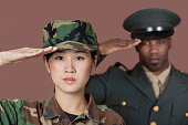Portrait of young female Marine Corps soldier and male officer saluting over brown background
