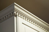 The top crown moulding dentil detail on some creme-color painted solid wood kitchen cabinets. These wall mounted cabinets do not go all the way to the ceiling above them. The lighting is coming from t