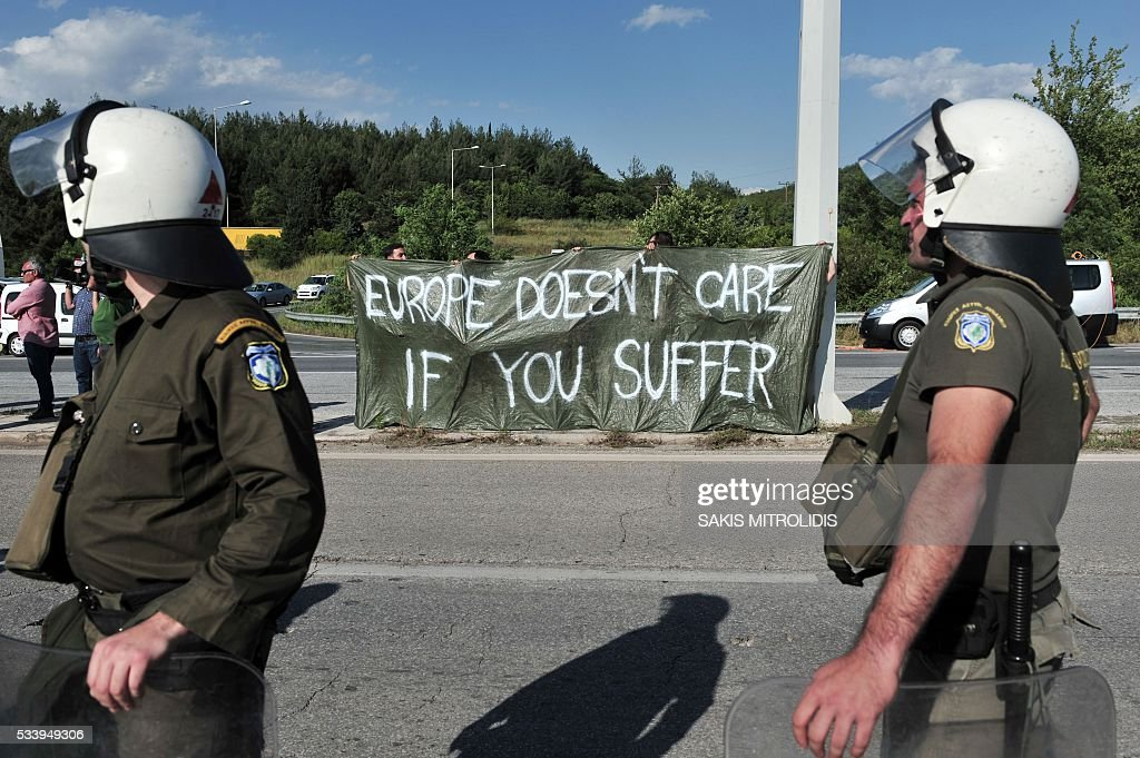 Solidarity groups hold a sign reading 'Europe doesn't care if you suffer' during a protest against the forced evacuation of migrants and refugees from a makeshift camp close to the Greece-Macedonia border, near the village of Idomeni on May 24, 2016. Greek police on May 24 moved hundreds of migrants out of the overcrowded camp of Idomeni, launching a major operation to clear up the squalid tent city where thousands fleeing war and poverty had lived for months. In an operation that began shortly after sunrise, Greek police said they had put more than 1,500 people on buses to newly opened camps near Greece's second city Thessaloniki, about 80 kilometres (50 miles) to the south. MITROLIDIS