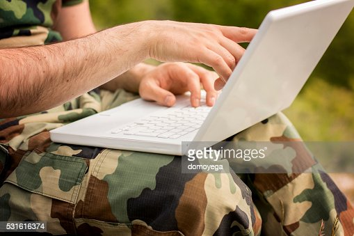 Solider on laptop, close-up : Stock Photo