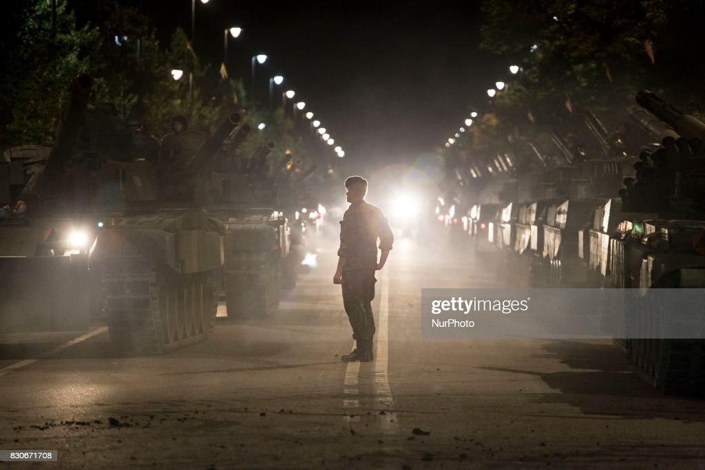 Solider stays near tanks during night training before parade on Polish Army Day in Warsaw on August 12, 2017.