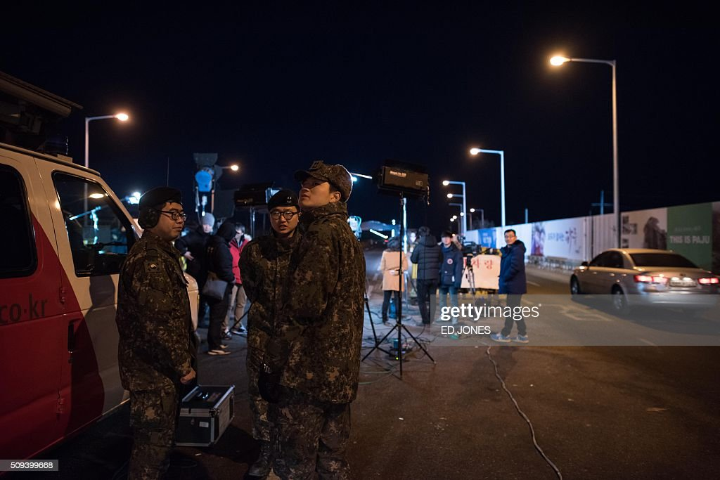 Soliders and media gather at the Tongil bridge, a checkpoint leading to the Kaesong joint industrial zone, in Paju on February 11, 2016. South Korea said it would suspend operations at the Kaesong joint industrial complex in North Korea to punish Pyongyang for its latest rocket launch and nuclear test. / AFP / ED JONES