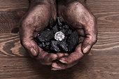 Solitaire diamond in hand full of coal