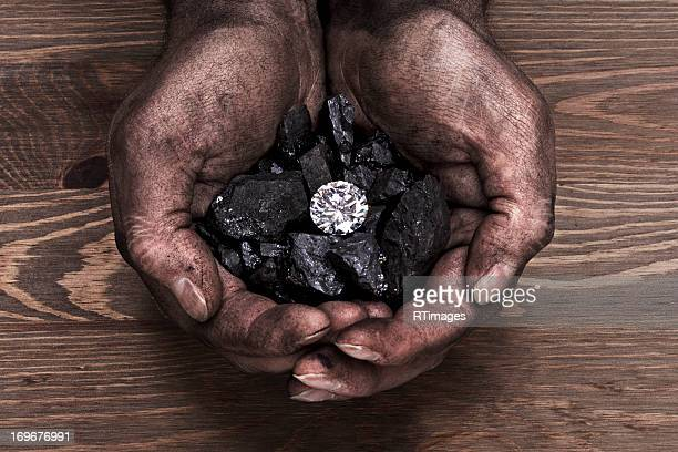 Solitaire diamond in hand full of coal