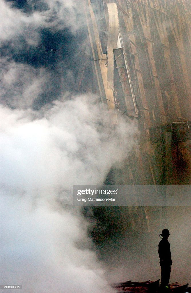A solitary fire fighter standing amidst rubble and smoke from fires still burning days after the Sept. 11 terrorist attack on the World Trade Center.