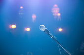 Solitary microphone and spotlights in smoky nightclub