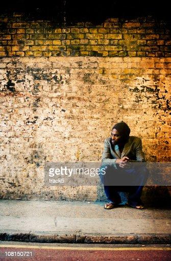 Solitary urban character sitting waiting by a brick wall